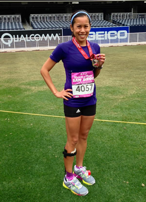Cheryl Hile, in running attire, standing on a field holding up a medal after a race.